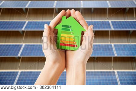 sustainability and consumption concept - close up of hands holding house with energy efficiency rating over solar panels on background
