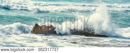 Close Up Of A Wave Crashing Against The Rocks In Porto Ferro Shore. Sardinia, Italy