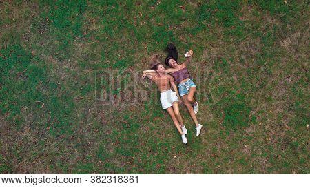 couple of friends lying on a meadow take a selfie