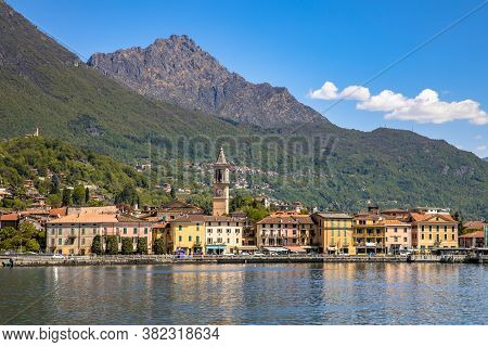 View Of City Of Porlezza On The Shore Of Lake Lugano With The Alps In The Background Seen From Lake,