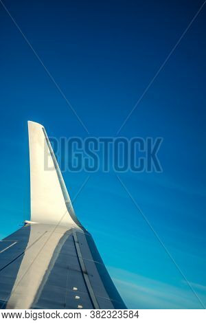Commercial Airplane Winglet Flying In A Blue Sky