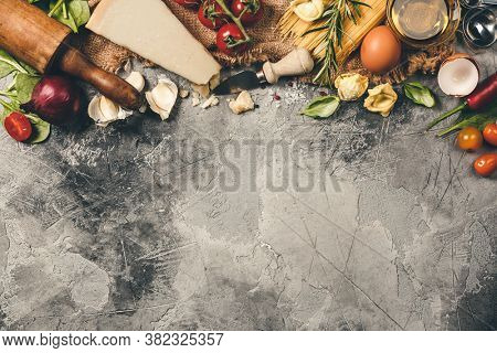 Italian food background with vine tomatoes, basil, spaghetti, spinach, onion, parmesan, olive oil, garlic, peppercorns rosemary and eggs Slate background