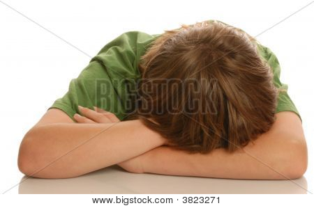Teen Boy With Head Down In Arms