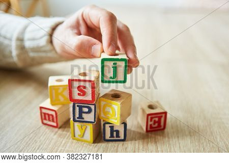 Hand of demented elderly woman stacks building blocks for learning and playing