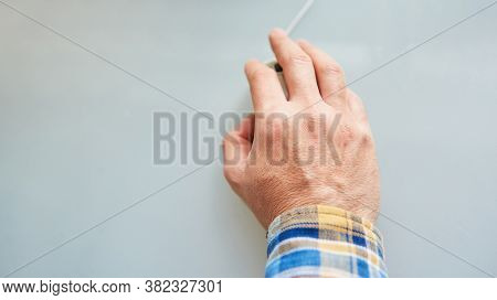 Hand of a senior operates a computer mouse in a computer class