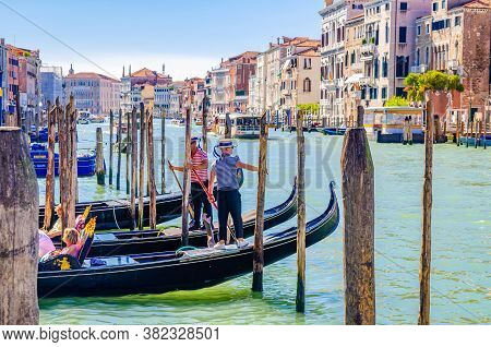 Venice, Italy, September 13, 2019: Gondoliers On Moored Gondolas Traditional Boats On Water Of Grand