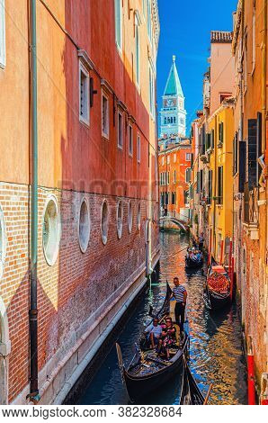 Venice, Italy, September 13, 2019: Gondolier On Gondola Traditional Boat With Tourists People Sailin