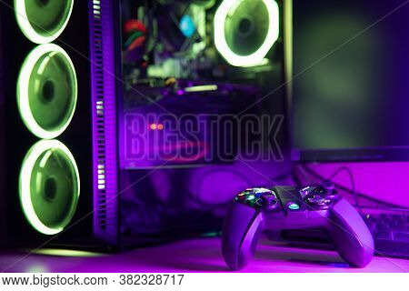 Game Controller And Glass Pc Case With Rgb Lighting On A Wooden Desk