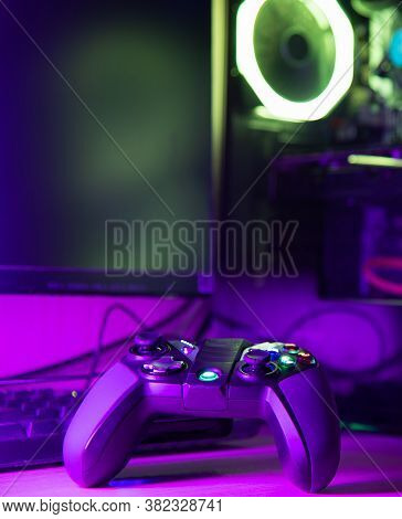 Close Up Of A Game Controller And Glass Pc Case With Rgb Lighting On A Wooden Desk