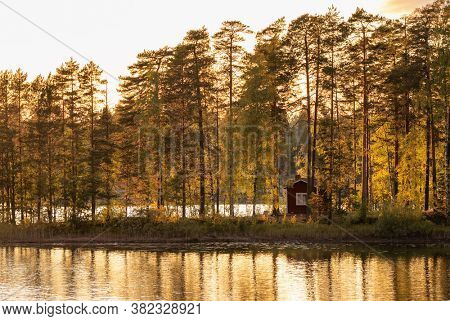 Small island on the lake with a country house in Finland. Traditional finnish lake landscape with cottage house at sunset
