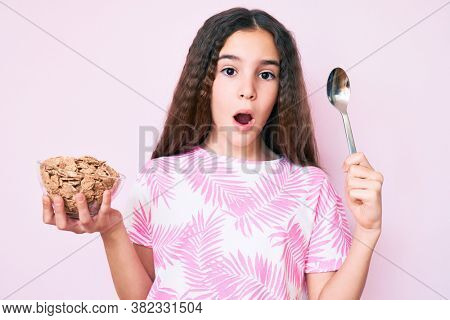 Cute hispanic girl holding cornflakes and spoon in shock face, looking skeptical and sarcastic, surprised with open mouth