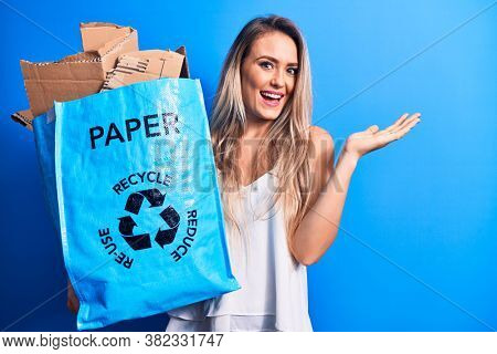 Young beautiful blonde woman recycling holding paper recycle bag full of paperboard celebrating achievement with happy smile and winner expression with raised hand