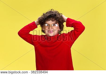 Shocked. Portrait Of Pretty Young Curly Boy In Red Wear On Yellow Studio Background. Childhood, Expr