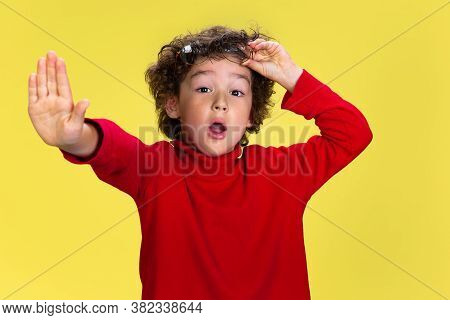Shocked Stopping. Portrait Of Pretty Young Curly Boy In Red Wear On Yellow Studio Background. Childh