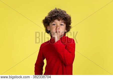 Whispering. Portrait Of Pretty Young Curly Boy In Red Wear On Yellow Studio Background. Childhood, E