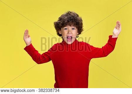 Showing Huge. Portrait Of Pretty Young Curly Boy In Red Wear On Yellow Studio Background. Childhood,