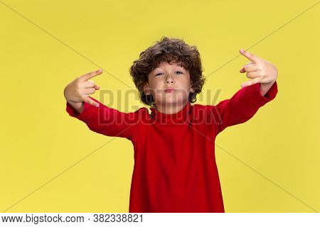 Rock Sign. Portrait Of Pretty Young Curly Boy In Red Wear On Yellow Studio Background. Childhood, Ex