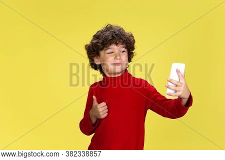 Using Smartphone. Portrait Of Pretty Young Curly Boy In Red Wear On Yellow Studio Background. Childh