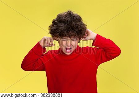 Closing Ears. Portrait Of Pretty Young Curly Boy In Red Wear On Yellow Studio Background. Childhood,
