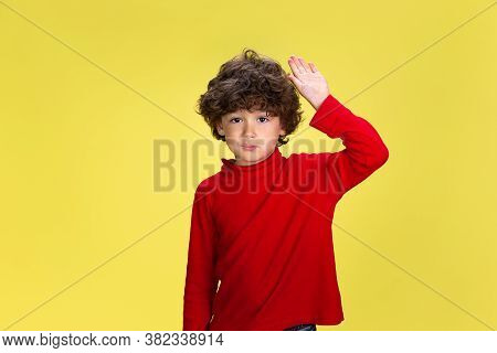 Greeting. Portrait Of Pretty Young Curly Boy In Red Wear On Yellow Studio Background. Childhood, Exp
