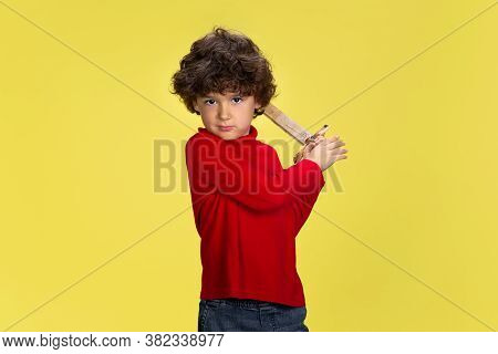 Warrior. Portrait Of Pretty Young Curly Boy In Red Wear On Yellow Studio Background. Childhood, Expr