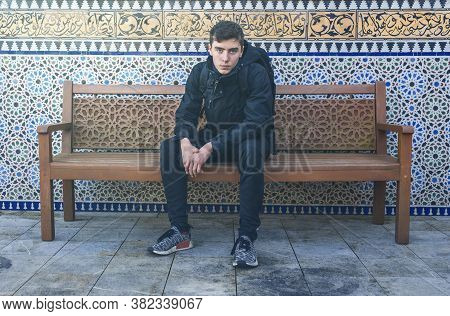 Portrait Of A Young Man Sitting On A Bench With Ornaments In The Background