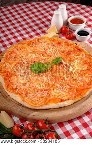Neapolitan Pizza With Parmesan Cheese, Slices Of Tomato, Fresh Basil And Tomatoes Sauce, Served On A
