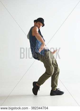 Stylish Young Guy Breakdancer In Hat Dancing Hip-hop In Studio Isolated On White Background. Break D