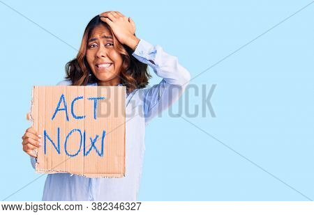 Young beautiful mixed race woman holding act now banner stressed and frustrated with hand on head, surprised and angry face