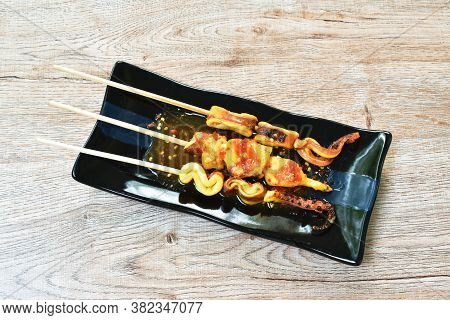 Grilled Squid Dressing Spicy Sauce Stabbing Wooden Stick On Black Plate