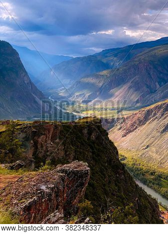 Beautiful mountain view with sunrays throw the dark clouds