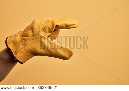 Hand of caucasian young man with gardener glove over isolated yellow background picking and taking invisible thing, holding object with fingers showing space