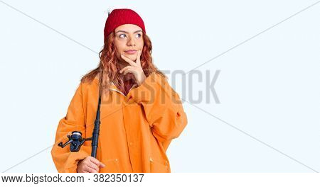 Young latin woman wearing fisher raicoat holding rod serious face thinking about question with hand on chin, thoughtful about confusing idea