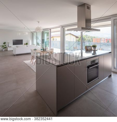 Modern kitchen with island, oven, induction plate and hood. Behind the table and sofa. Nobody inside