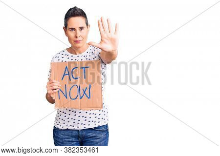 Young woman with short hair holding act now banner with open hand doing stop sign with serious and confident expression, defense gesture