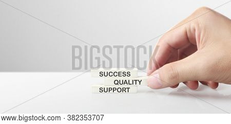 Cube with words success, company, support, quali ty, mission, business, in hand. personal development