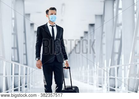 Handsome Young Businessman In Protective Mask Walking By Airport, Carrying Luggage, Having Business