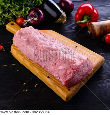 Raw Fillet Of Pork On Wooden Cutting Board On Dark Background And Blank Space For Your Text. Tenderl
