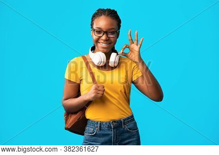 Okay. African Student Girl Gesturing Ok Sign Posing With Backpack Smiling To Camera Over Blue Backgr
