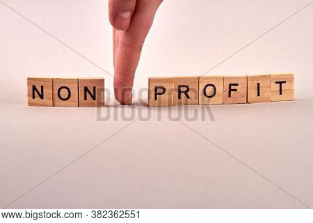 Wooden Blocks With Letters Making Non Profit Text. Hand Between Wooden Blocks. Isolated On White Bac