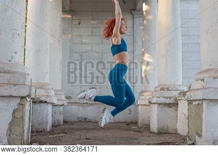 Young Red-haired Sportswoman Jumping In The Air. In A Turquoise Tracksuit, Leggings, Against The Bac
