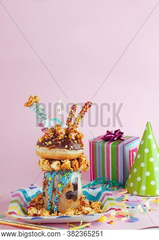 Freak Shake With Donut And Caramel Popcorn On The Party Background With Copy Space