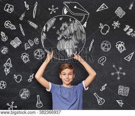 Online Education In School. Inspired Teenage Boy Getting Good Education, Holding Globe With Graduati