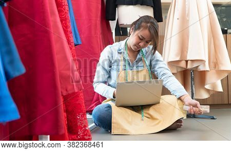 Stressed Asian Entrepreneur Sitting Beside The Window Because Her Shop Has Stopped Doing Business. D