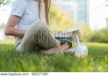 Cropped Young Student Woman With Books Spends Free Leisure Time While Sitting On The Grass Outside I