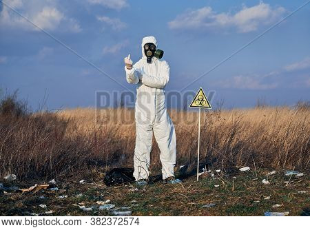 Angry Ecologist In Protective Coverall And Gas Mask Standing In Field With Garbage And Biohazard War