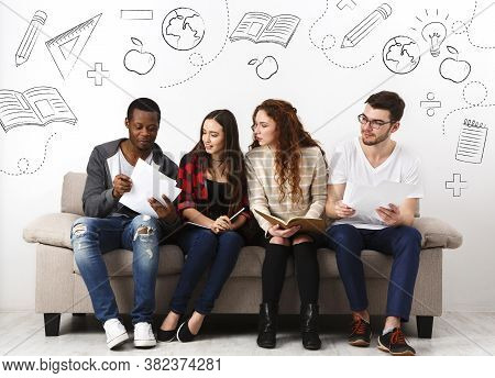 Diverse Young Students Preparing For Exam, Sitting On Sofa Over White Backgroud And Studying, Studio
