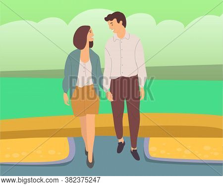 Couple Walking Down The Street. Young Guy And Girl Holding Hands, Looking At Each Other, Walking In