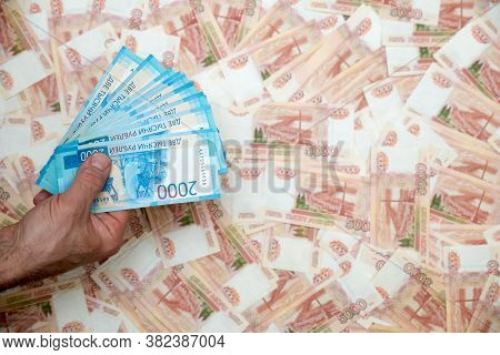 A Mans Hand Holds Russian Money Worth Two Thousand Rubles In Close-up Against The Background Of Five