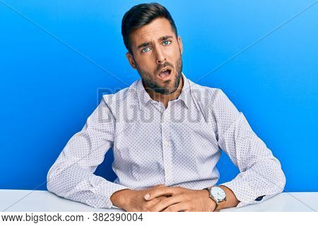 Handsome hispanic man wearing business clothes sitting on the table in shock face, looking skeptical and sarcastic, surprised with open mouth